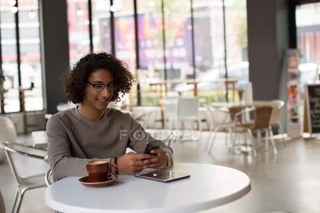 Happy man using mobile phone in restaurant — Stock Photo