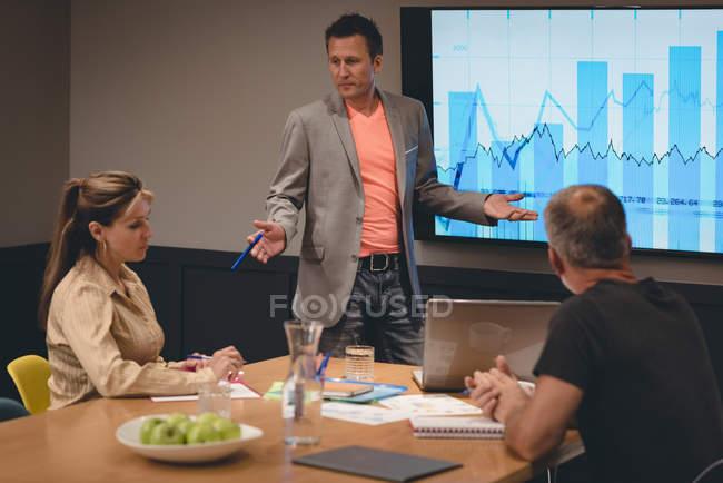 Empresário fará apresentação aos colegas na sala na sala de reuniões — Fotografia de Stock
