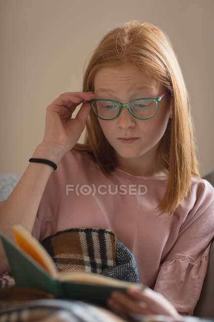 Дівчина, читаючи книгу в вітальня в домашніх умовах — стокове фото