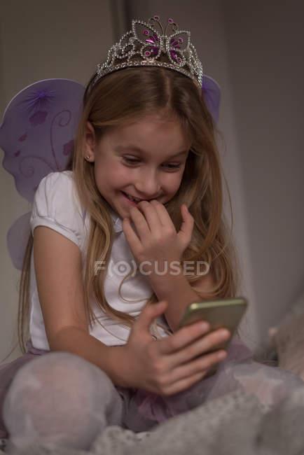 Дівчина, що використання мобільного телефону у спальні будинку — стокове фото