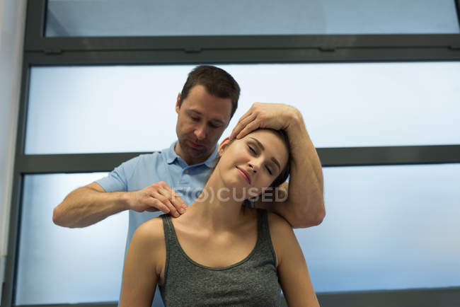 Fisioterapista che fa un massaggio alla donna in clinica — Foto stock