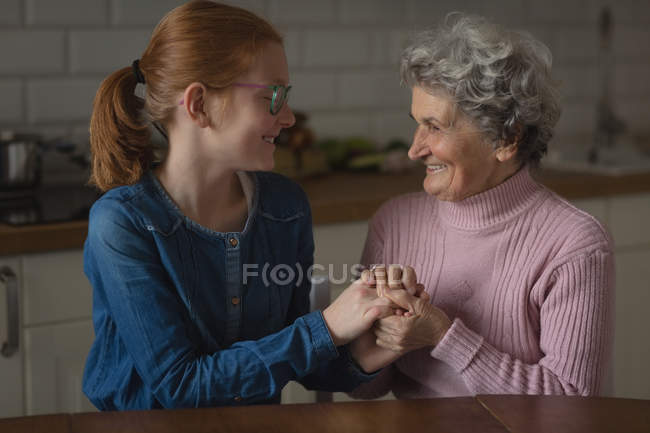 Grandmother and granddaughter interacting with each other in kitchen at home — Stock Photo