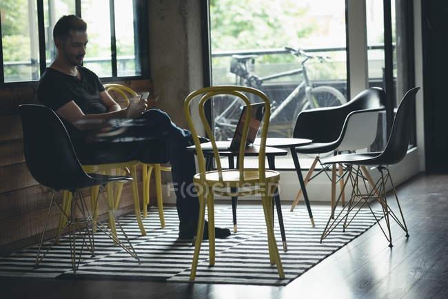 Бизнесмен с помощью мобильного телефона в офисе — стоковое фото