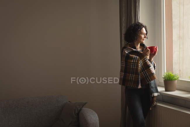 Donna premurosa che prende un caffè in soggiorno a casa — Foto stock