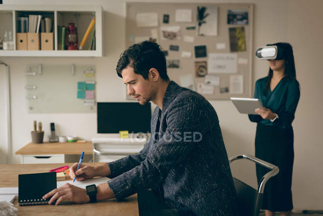 Male executive writing on paper at desk in office — Stock Photo