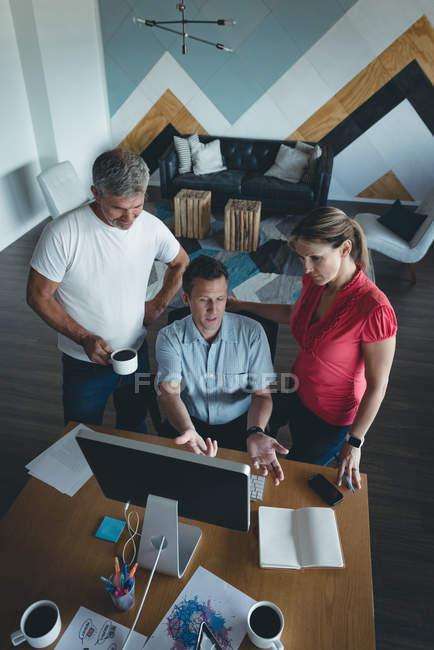 Compañeros de negocios discutiendo sobre computadora en el escritorio en la oficina - foto de stock