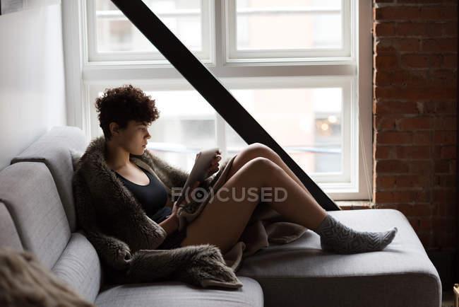 Belle femme utilisant une tablette numérique tout en se relaxant sur le canapé à la maison — Photo de stock