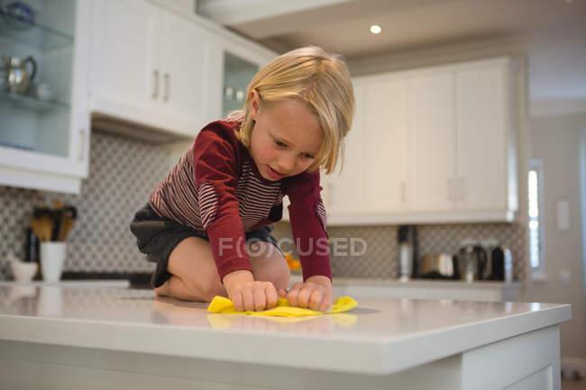 Garçon nettoyage plan de travail de cuisine avec chiffon à la maison — Photo de stock