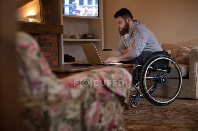 Jeune homme handicapé utilisant un ordinateur portable à la maison — Photo de stock