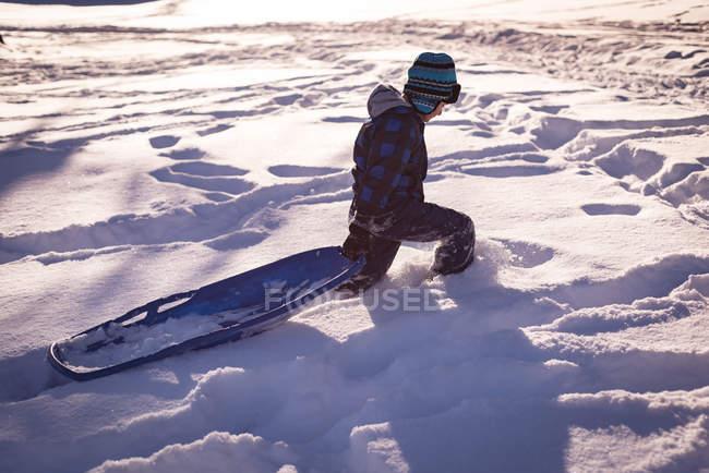 Chica caminando con trineo en la nieve durante el invierno - foto de stock