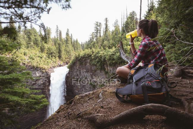 Frau sitzt am Wasserfall und trinkt Wasser an einem sonnigen Tag — Stockfoto