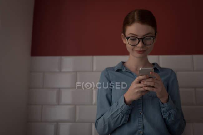 Mulher usando um telefone celular na cozinha em casa — Fotografia de Stock