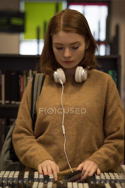 Giovane donna raccogliendo cassetta dalla biblioteca — Foto stock