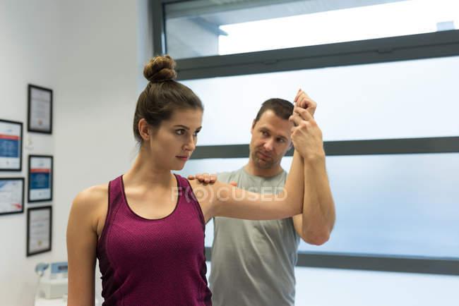 Fisioterapista che fa un massaggio alle mani alla donna in clinica — Foto stock