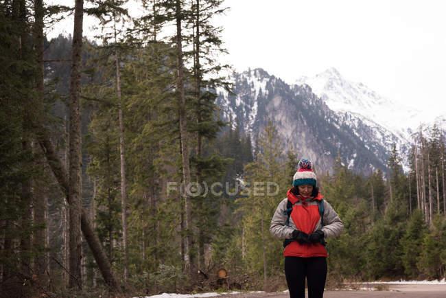 Женщина, регулируя рюкзак поясом на талии в зимний период — стоковое фото