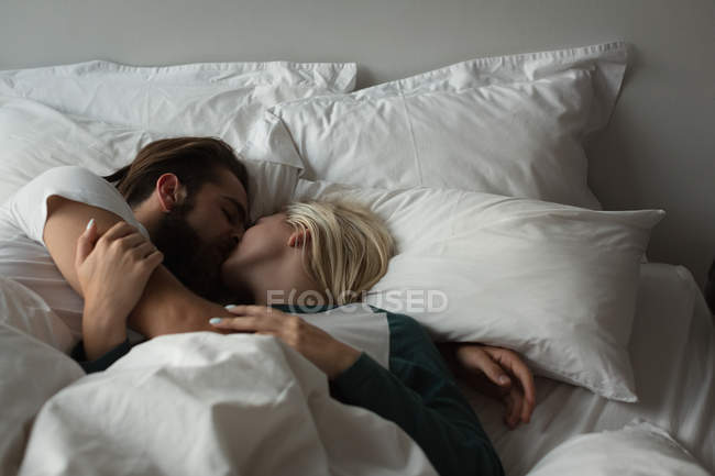 Couple kissing each other in bedroom at home — Stock Photo