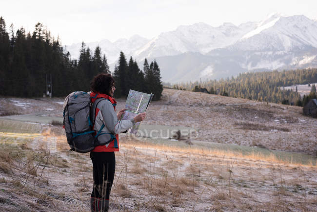 Woman looking at map while hiking during winter — Stock Photo