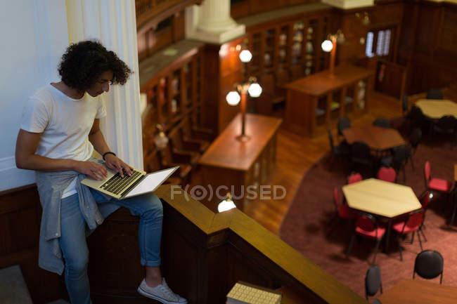 Giovane che utilizza computer portatile nella libreria — Foto stock
