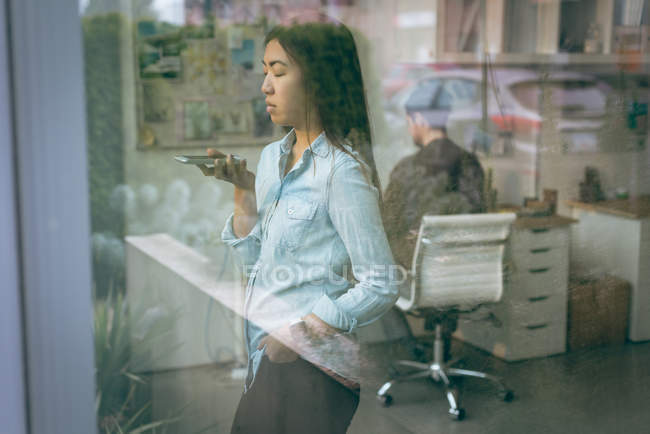 Female executive talking on mobile phone in office — Stock Photo