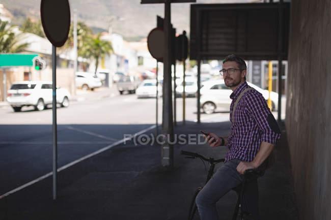 Bell'uomo con il cellulare in piedi sul marciapiede — Foto stock