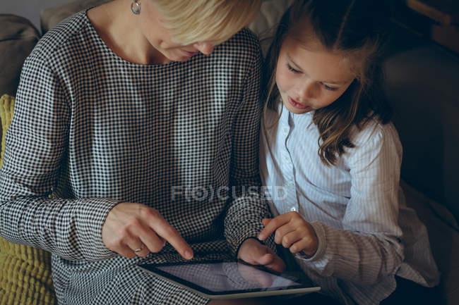 Мать и дочь с помощью цифрового планшета дома — стоковое фото