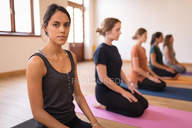 Группа женщин медитирует вместе в фитнес-клубе — стоковое фото