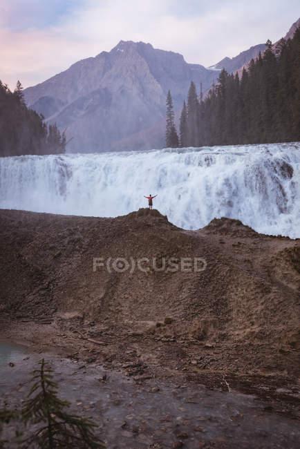 Visão traseira do homem de pé com os braços estendidos perto da cachoeira — Fotografia de Stock
