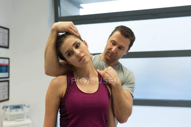 Fisioterapista che fa un massaggio al collo alla donna in clinica — Foto stock