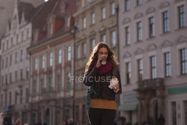 Молода жінка, каву і сніданку на вулиці — стокове фото