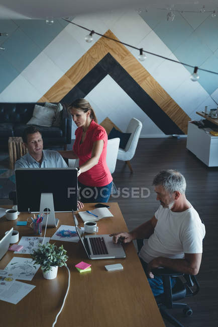 Business colleagues discussing over computer at desk in office — Stock Photo