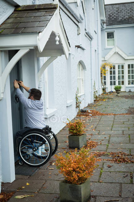 Disabled man opening the door of his home — Stock Photo