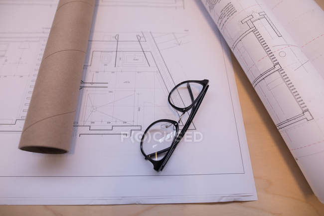 Blueprint and spectacle on table in office — Stock Photo