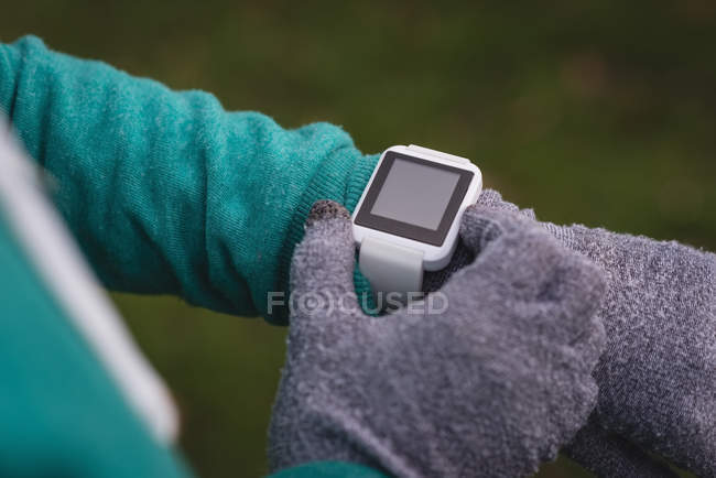 Close-up of woman using smartwatch in the park — Stock Photo