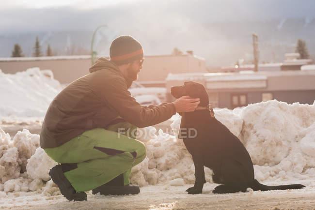 Mann streichelt seinen Hund im Winter am Straßenrand — Stockfoto