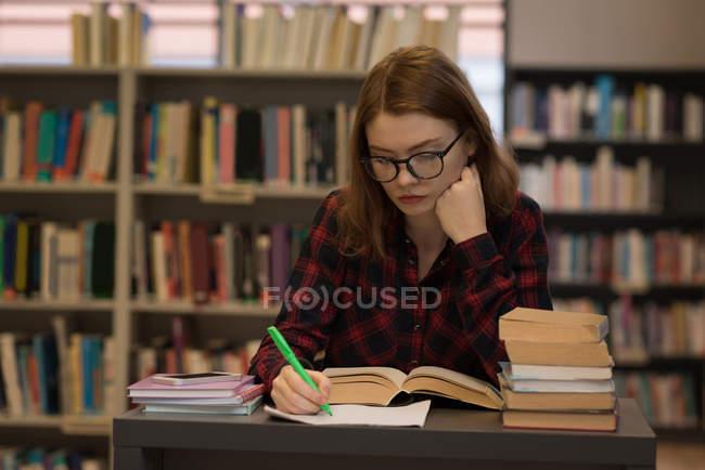 Jeune femme écrivant sur papier à la bibliothèque — Photo de stock