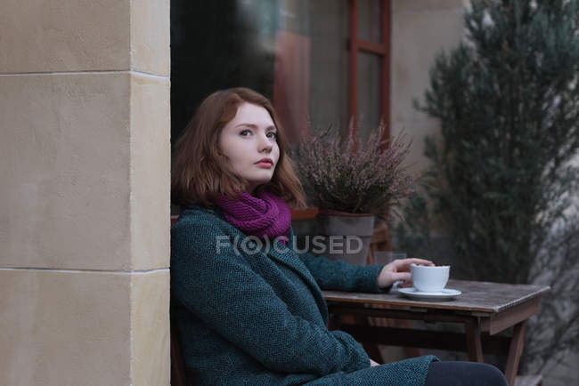 Thoughtful woman having cup of coffee at outdoor cafe — Stock Photo