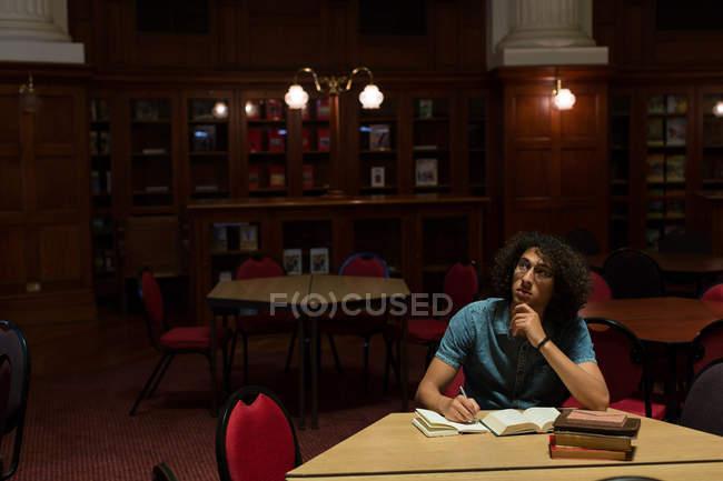 Giovane, studiando in biblioteca — Foto stock