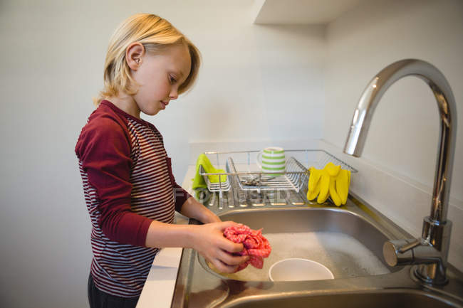 Boy washing a rag cloth in kitchen at home — Stock Photo