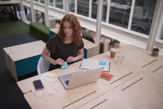 Female executive holding sticky note at desk in office — Stock Photo