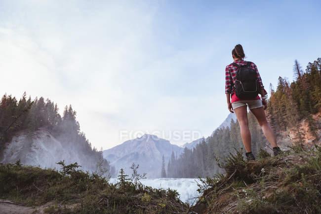Vista posteriore della donna con lo zaino guardando la cascata — Foto stock