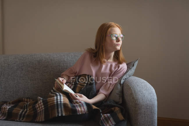 Thoughtful girl reading a book in living room at home — Stock Photo