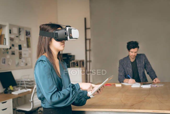 Жіночий виконавчий, використовуючи гарнітуру віртуальної реальності і цифровий планшетний в офісі — стокове фото