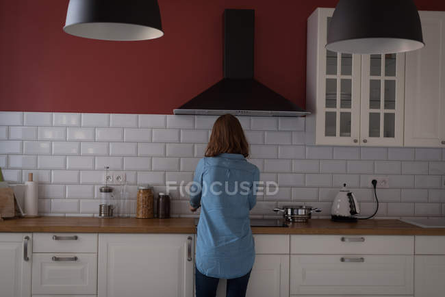 Rear view of woman working in the kitchen at home — Stock Photo