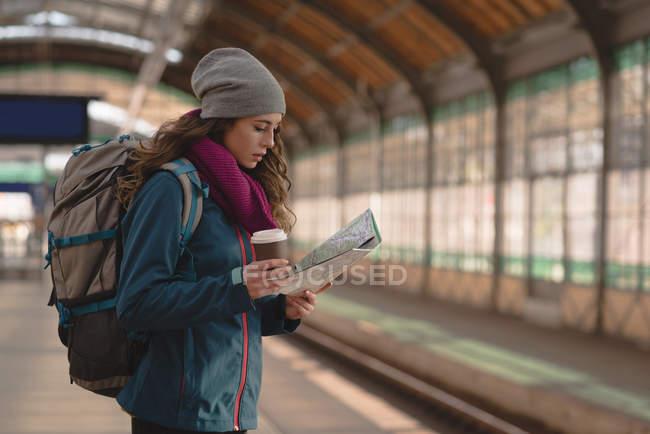 Jovem mulher olhando para o mapa enquanto toma café — Fotografia de Stock