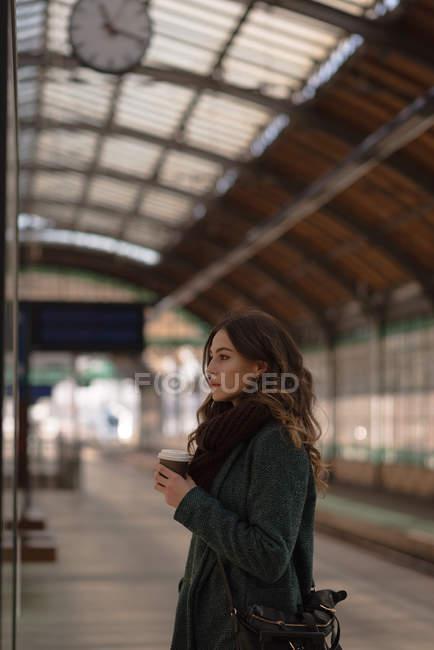 Femme réfléchie prenant un café à la gare — Photo de stock