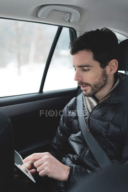 Young man using digital tablet in a car — Stock Photo