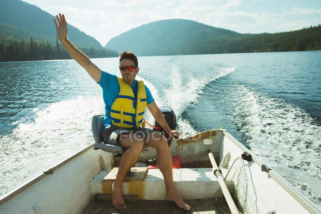 Homme voyageant en bateau à moteur sur un lac — Photo de stock