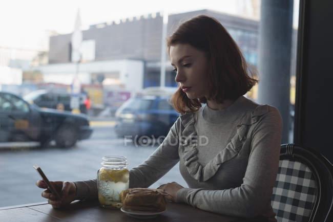 Seitenansicht einer Frau, die ihr Handy im Café benutzt — Stockfoto