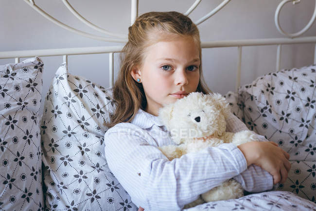 Portrait of girl playing holding teddy bear on bed — Stock Photo