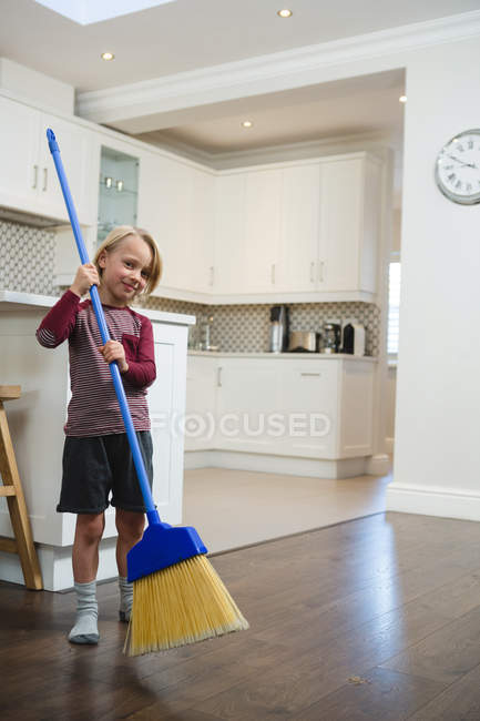 Boy cleaning floor with broom in kitchen at home — Stock Photo